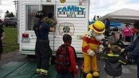 Sparky congratulates children for completing the the Family Safety House as Firefighter Hickey assists another child out of the window.