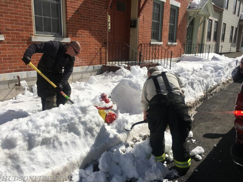 Mike McCrady and Wally Moore clearing snow from the buried hydrant in the previous photo.